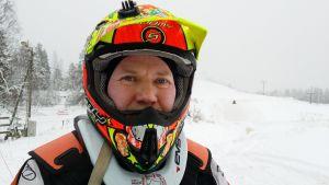 Ismo Määttälä lumisen rinteen äärellä kypärä päässään.