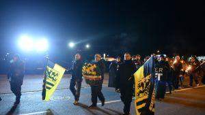 Miehiä marssii lippujen kanssa kadulla.