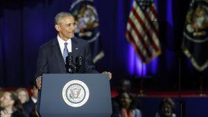 Obama hymyilee puhujapöntössä.