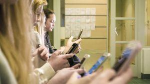 Lapset käyttävät kännyköitä koulun käytävällä.