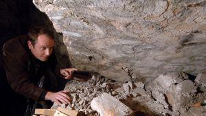 Weidner kumartuneena kivisen kaaren alle. Kaareen on maalattu koristeellisia kiemuroita.