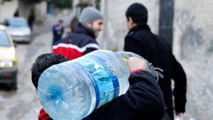 Mies kantaa vesipulloa.