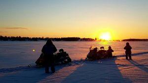 Moottorikelkkailijoita joen jäällä auringonlaskua vasten