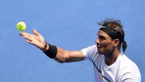 Rafael Nadal heittää pallon ilmaan.