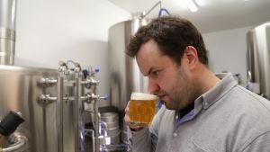 Panimoyrittäjä Mikko Suur-Uski tarkkailee oluen laatua paitsi maun osalta - myös sen tuoksua.