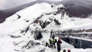 Lumisessa maisemassa hautautuneen hotellin raunioissa joukko pelastustyöntekijöitä kaivelee lunta. Taustalla näkyy harmaansävyisiä vuoria.