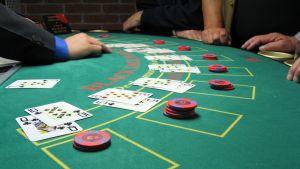 Korttipeli Blackjackiä pelataan pelipöydällä.