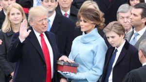 Trump vannoo virkavalaansa, toinen käsi pystyssö, toinen raamatulla, jota pitelee hänen vaimonsa Melania Trump.