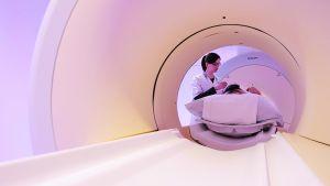 Hoitaja valmistelee potilasta magneettikuvaukseen.