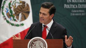Tummaan pukuun pukutunut mies puhujankorokeen takana, miehellä on punainen kravatti, taustalle Meksikon lippu.
