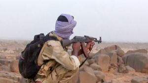 sotilas kivääri kädessään aavikolla