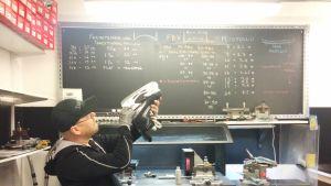 Mies katsoo luistimen terää teroituskoneen edessä. Taustalla liitutaulu, johon on kirjoitettu muotoilussa tarvittavia mittoja.