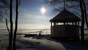 Aurinko paistaa ja hiihtolatu lähtee rannasta Perämerelle.