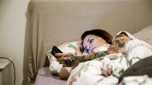 nainen katselee puhelinta vuoteessa