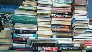Kirjahyllyn sisältö pinottuna. Mitä säilyttää? Mitä viedä kiertoon?