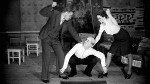 Lavalla käynnissä iltamat. Yksi mies on kyykyssä lattialla ja toinen mies ja nainen puivat nyrkkiiään tämän molemminpuolin.