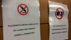 Oikeussalin ovi, johon kiinnitetty kuvaamisesta ja nauhoittamisesta kertovat kiellot.