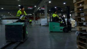 Kaksi logistiikan opiskelijaa ajaa trukilla logistiikkakeskuksessa.