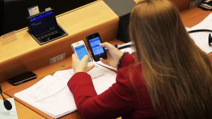Meppi naputtelee kahta kännykkää istuntosalissa.