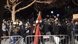 Mielenosoittajia käsissään megafoneja ja lippuja.