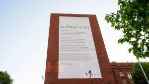 Punatiilirakennuksen seinää kiinnitetty suuri juliste, johon on painettu runo.