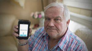 Kari Forsell pitelee kädessään iPodia, jolla hän säätelee kehoonsa asennettua stimulaattoria.