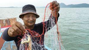 Kalastaja Sompol Muakpradab on tyytyväinen pienestäkin katkarapusaaliista.