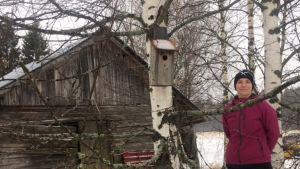 Lammin tilan emäntä Viivi Huuskonen seisoo puun vieressä. Puuhun kiinnitettynä Miljoona linnunpönttöä -kampanjaan ilmoitettu pönttö. Taustalla maatilan pihapiirin vanha lato.