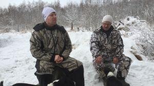Kaksi miestä ja kaksi koiraa lumisessa metsässä.