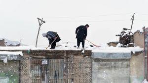 Miehet lapioivat lunta talon katolla kabulissa.