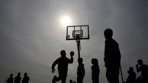 Lapset pelaavat koripalloa pakolaileirillä.