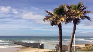 """Nykyinen """"muuri"""" Tijuanan kohdalla ulottuu Tyyneenmereen asti. Rajan  takana avautuu hiekkarannan jälkeen San Diegon kaupunki Yhdysvalloissa."""