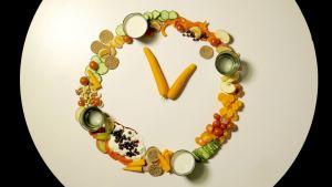 Seniorin ruokakoulun tunnuskuva, kasviksista koottu kello.