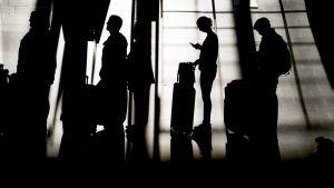 matkustajat jonottavat matkavaroineen lentokentällä