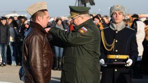 Kenraalieversti Aleksandr Galkin (oik.) kiinnittää kunniamitalin Syyriasta palanneen lentäjän rintaan Venäjän Krasnodarissa maaliskuussa 2016.