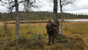 Metsästäjä suolammen lähellä puiden vieressä Kuusamossa.
