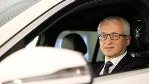 Mies istuu autossa kuljettajan paikalla ja katsoo ulos avonaisesta ikkunasta.