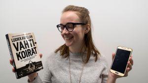 Nuori Anni toisessa kädessään kirja ja toisessa kännykkä.