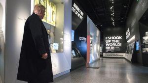 """Trump kulkee museon käytävällä mustassa päällystakissa. Käytävän päässä näkyy nyrkkeilijä Muhammad Alin valokuva ja mustalla pohjalla suurilla valkoisilla kirjaimilla teksti: """"I shook up the world!"""" eli """"Ravistelin maailmaa!"""""""