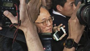 Donald Tsang kuvaajien ympäröimänä.