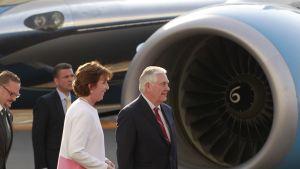 Tummassa puvassa ja punaisessa kravatissa kulkeva Tillerson ohittaa juuri lentokoneen valtavaa moottoria. Hänen vierellään kulkee Yhdysvaltain Meksikon-suurlähettiläs Roberta Jacobsen. Taustalla kulkee vielä kaksi tummapukuista miestä.