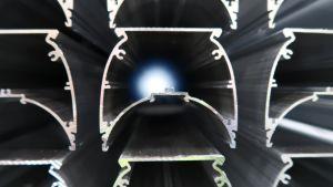 Alumiinista tehtyjä profiileja, joiden takaa loistaa valoa.
