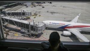 Mies istuu Kuala Lumpurin lentokentällä ja katselee lentokoneita.