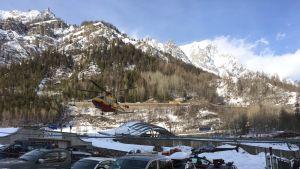 Lumivyöryssä loukkaantuneet kuljetettiin helikopterilla sairaalaan Cormayeurista 2.3. 2017. Kuvassa parkkipaikkaa, autoja, helikopteri ilmassa ja taustalla vuorenhuippuja.