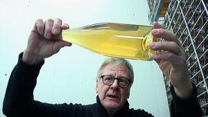 Juhani Salovaara tarkastelee viinipulloa.