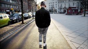 Nuori mies kävelee kadulla.