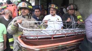 Pelastajat pitelivät telinettä, jolla ruumiita kannettiin palaneesta lastenkodista San José Pinulassa Guatemalassa keskiviikkona 8. maaliskuuta 2017.