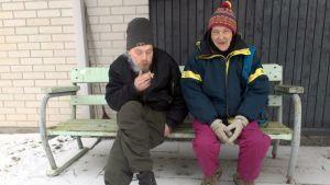Nainen ja Mies talon edustalla puistonpenkillä. Mies polttaa tupakkaa ja nainen nauraa silmät sirrissä.