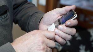 vanhempi mies pitää kännykkää kädessä