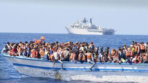 Vene täynnä pakolaisia ja iso laiva taustalla.